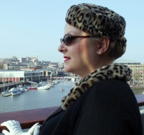 Me on the balcony at MShed Museum. To create the look, I took an old Marks and Spencers faux-fur hat, cut-off the brim and fashioned a pillbox style hat. The brim I attached to the neck of an old black, button-through cardigan to create a stylish collar. I removed the buttons of the cardigan and replaced with pearl-look buttons. I borrowed an original pair of white 1950s gloves from my mother-in-law. The stockings I wore were original 1950s, they tended to lose their shape as there was no lycra in them. I wore a 1950s style girdle brought from the London based vintage shapewear specialists What Katie Did. The handbag is an original on loan from my dear friend Carolyn Hair.