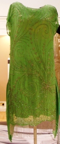 Light green chiffon dress, tabard style, with wide shallow scooped neckline.  Decorated asymmetrically with a bold design of silver bugle beads. C.1925-27.Weight 406g.Dazzle Exhibition. BWM1963.161. Hampshire County Council Arts and Museums Service (HCC Arts & Museums).