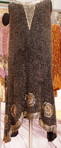 Black, open weave dress decorated with silver and gold bugle beads and sequins. There is a striking narrow V to the neckline, with collar band reminiscent of Egyptian design. The beads are sewn on machine stitch using a tambour. Rivis Collection. C.1926-28. Weight 904g. Dazzle Exhibition. C.1976.31.48. HCC Arts & Museums.