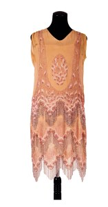 Salmon pink and silver dress decorated in pink faceted rocailles, pale pink bugle beads and silver lozenge shaped beads. The beaded fringe would have created movement when dancing the dress is constructed in three layers, with the bottom layer forming the lining. Weighs 914g.C. 1925-27. C.1996.116. HCC Arts & Museums.