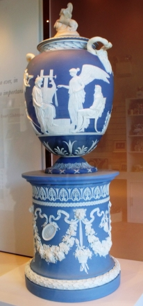 The Apotheosis of Homer Vase. Cylindrical pedestal with white reliefs of fruiting vines, medallions, lions' heads, ribbons and trophies. Solid blue Jasper Relief decoration modelled by John Flaxman. C.1790.