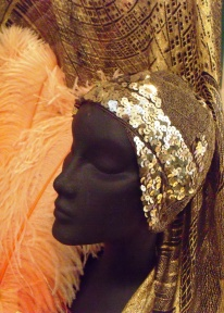 Shawl, feathers and cap of bronze mesh with gold sequins. C.1928. Dazzle Exhibition. HCC Arts & Museums.