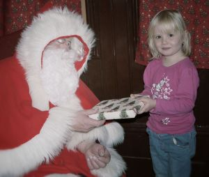 Following her visit to his grotton, a delighted little girl receives her gift from Father Christmas. Milestones.