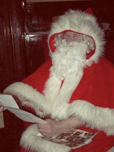 Father Christmas reading letters and Christmas lists at Milestones.