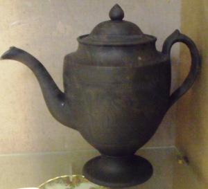 A coffee pot, Spode, C. 1805. Basaltware (a type of stoneware), hand-thrown then turned on a lathe to create the precise shape, smooth surface and tooled decoration. On display at Bristol Museum and Art Gallery.