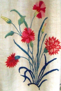 Embroidered detail of the curtains around Gilbert's bed.