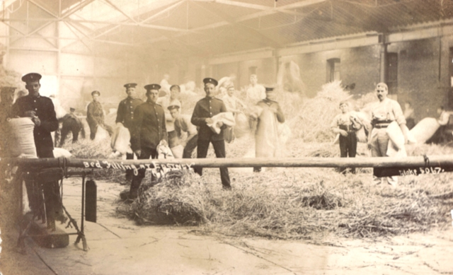 Royal Marine Artillery filling beds with straw in Drill Hall of the Royal Marine Artillery Barracks, Eastney, c1910. Kalamazoo number: 2/7/6 (48). © Courtesy of the Trustees of the Royal Marines Museum.