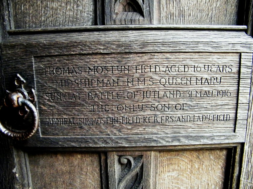 One of the more unusual World War One memorials that I have come across in the New Forest. This one is carved into the doors at the entrance of East Boldre Church (not far from Brockenhurst). Thomas Mostyn Field was born in 1900 and died on 31st May, 1916, aged 16. He died, along with 57 Officers and 1,209 men, who sank when their ship HMS Queen Mary was involved in enemy action at the Battle of Jutland. Thomas had become a Naval Cadet at the age of 13 and was serving as a Midshipman when he died. He was the only son of Admiral Sir Arthur Mostyn Field (1855-1950) KCB FRS and his wife Lady Field. ©Come Step Back in Time.