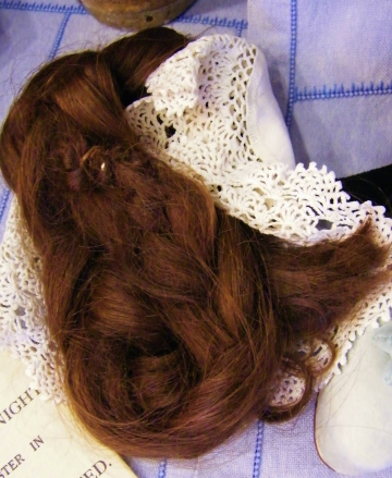 One of the more unusual items in Lucy's collection is this long, thick plait of brown hair. It belonged to one Ethel Haselhurst. Ethel wanted freedom from the impracticalities of having long hair so decided to cut her plait off in 1918. Lucy told us that many women cut their long, pre-war, hair during World War One. Shorter styles continued to be preferred by women after the war. Practicality gave way to fashionability and the boyish cuts of the roaring twenties. When the 'bob' and 'shingle' cuts were de-regar.