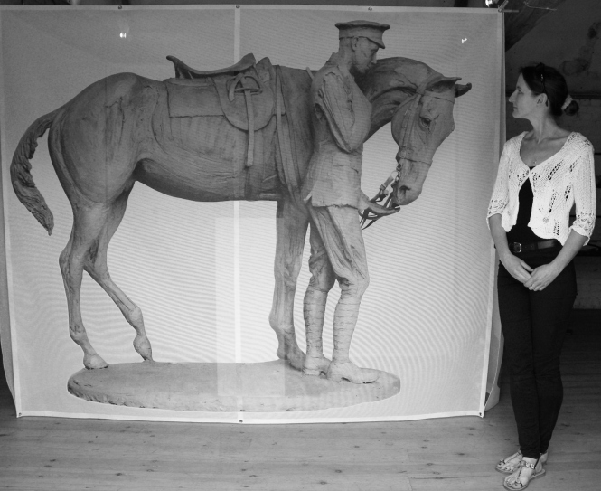 Sculptor Amy Goodman with a life-size image of the Romsey War Horse and Trooper that she has designed. Photograph taken at the Ranvilles Farm, pop-up exhibition, July 2014. ©Come Step Back In Time.