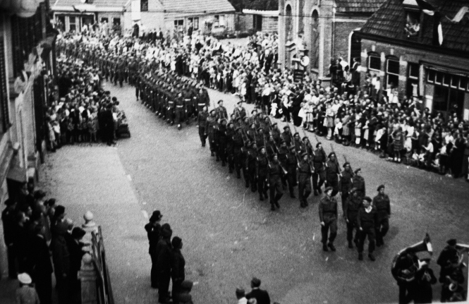 Hengelo Victory Parade 9th May, 1945. One of the photographs in my grandfather's collection, It shows his unit taking part in the event. Eric tells me that: 'The photo was taken in Burgemeester Jansenstraat. The street is there today but it has totally changed so you would not recognise it today.  The church in the far-side of the road was torn down in 1966. During the war civilian administration was located next to the church. Resistance fighters set fire to the administration building [after first being ransacked, then soaked with gasoline]so that the Nazis could not check whether someone had falsified ID cards, which had been issued by the resistance itself. A copy of all issued ID cards was kept at the administration office.'  ©Come Step Back In Time (The Langley Family Archive)