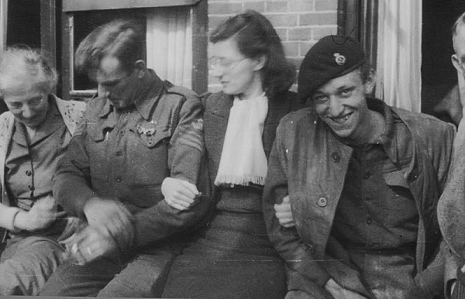 During the liberation of Hengelo, local citizen Mrs. A. Wilmink (centre)enjoying the company of Allied soldiers . Image courtesy of Eric Heijink (http://www.secondworldwar.nl/hengelo-1940-1945.php)